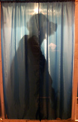 Ukrainian coal miner is seen through curtain in a booth at a polling station organized at a mine in ...