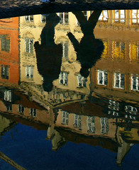 Two boys are reflected in the water of a fountain as they walk through the old town of Warsaw.
