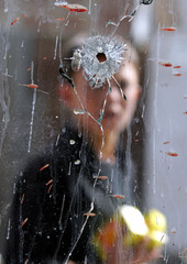 Afghan child looks at a hole on a shop window in Kabul.