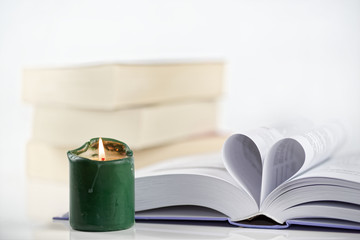 Heart shape from paper and burning green candle against white background.