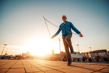 Athletic senior man running in the city
