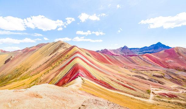 Panoramic view of Rainbow Mountain at Vinicunca mount in Peru - Travel and wanderlust concept exploring world nature wonders - Vivid multicolor filter with bright enhanced color tones