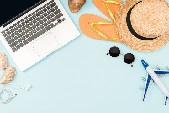 top view of toy plane, laptop with blank screen, headphones, sunglasses, seashells, flip flops, plane model and straw hat on blue background
