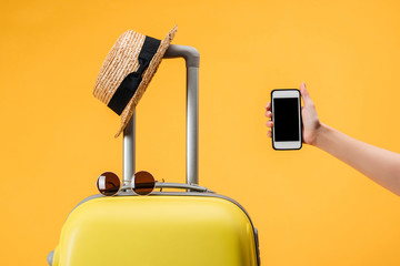 cropped view of woman holding smartphone with blank screen near travel bag, straw hat and sunglasses isolated on yellow