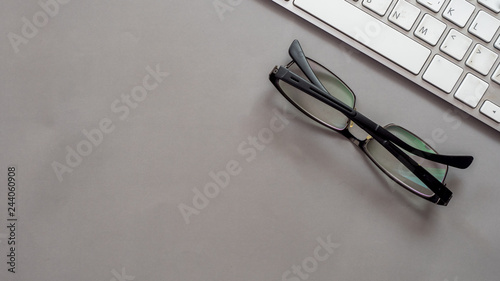 Wall mural glasses and keyboard top view on gray background business concept