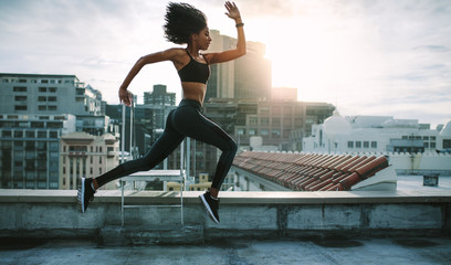 Athlete woman running on rooftop
