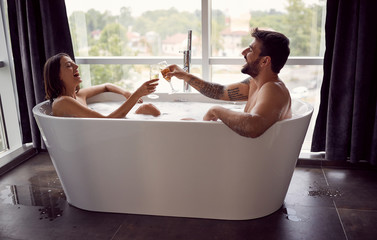 Smiling boy and girl have fun together in the bathtub and drinking champagne.