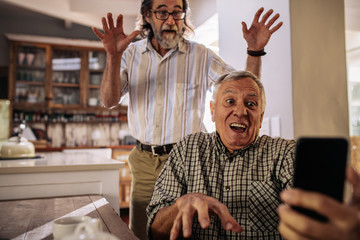 Retired men making funny faces while taking selfie