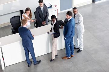 reception woman explains businessman.