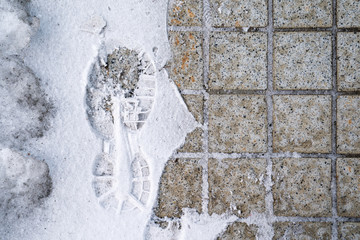footprint in snow with half side tile in image.