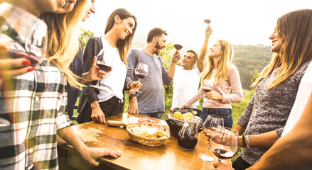 Millenial friends having fun time drinking red wine oudoors - Happy fancy people enjoying harvest at farmhouse vineyard winery - Youth friendship concept together at pic nic garden party - Warm filter