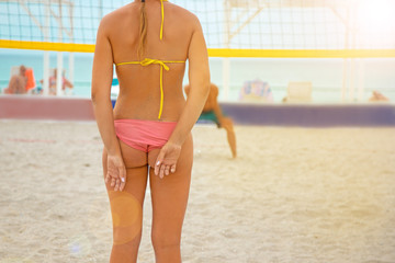 Volleyball beach player is a female athlete volleyball player making signs with her fingers behind her back on the beach.