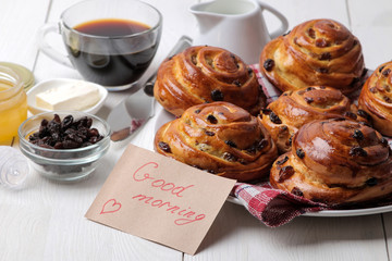 Tasty buns with raisins and coffee with milk on a white wooden background. fresh bakery. breakfast.
