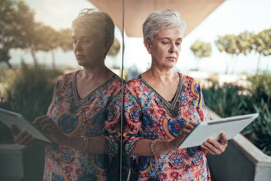 Portrait of a beautiful grey haired middle aged woman working on digital tablet