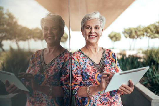 Portrait of a beautiful grey haired middle aged smiling woman working with tablet looking into the camera