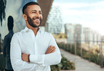 Portrait of a young confident smiling indian man with his arms crossed looking into the distance Wall mural