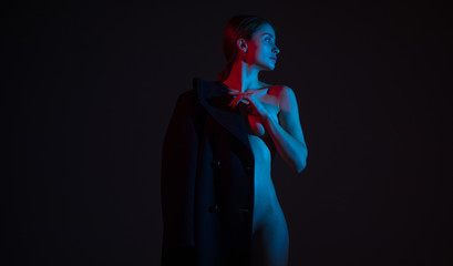 Young naked woman stands and poses covered coat.