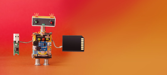 Media information storage electronic equipment concept. Robot with usb and memory card. Creative design robotic toy on red orange background. copy space Wall mural