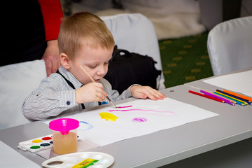 A little boy learns to paint with a brush on a piece of paper sitting at a table