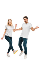 happy young couple in white t-shirts dancing and smiling at camera isolated on white
