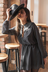Trendy sexy young female wearing casual clothes posing over old cafe room