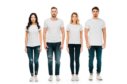 full length view of serious young men and women in white t-shirts and denim pants standing and looking at camera isolated on white