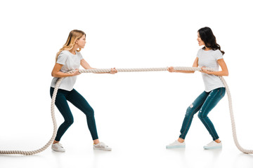 angry young women pulling rope and looking at each other isolated on white