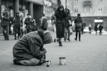 Elderly beggar woman on the street asking for money. Beggars. Social problem. Black and white. Social issue