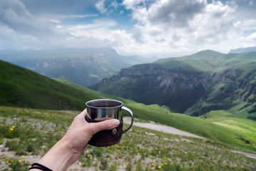 first-person view female hand with a mug of tea on a background of mountains