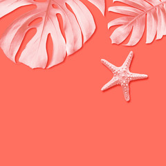 Starfish and summer tropical leaves on living coral background with copy space