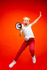 Beautiful young child teen girl jumping with megaphone isolated over red background. Runnin girl in motion or movement. Human emotions,, facial expressions and advertising concept