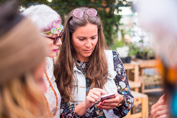 Hippy fashion style trendy group of mixed ages caucasian women using technology modern phone together - beautiful females with coloured dress and clothes enjoying internet device