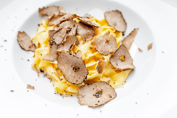 Dish of delicious italian pasta with truffle mushroom chips, on the table in luxury restaurant.