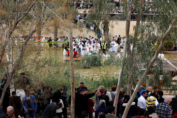 Pilgrims take pictures as others take a dip in the waters of the Jordan River during a baptism ceremony at the Qasr el-Yahud site