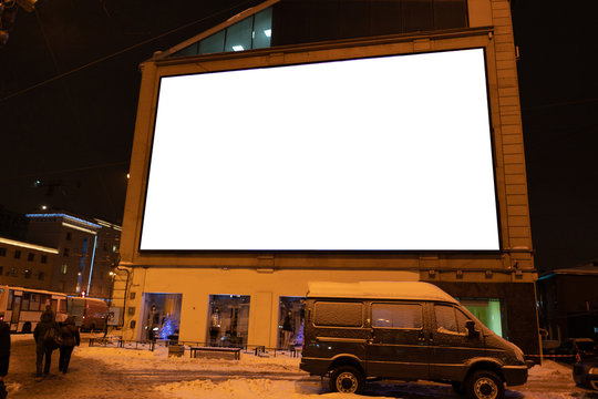 large LED screen on the wall of the house. outdoor advertising screen glowing at night