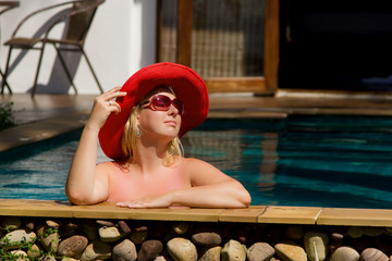 Young blonde beautiful woman in sunglasses in swimming pool bathing