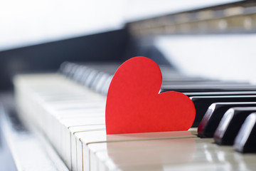 Red bright heart on a keyboard of an old piano. Cocept of love, valentine's day