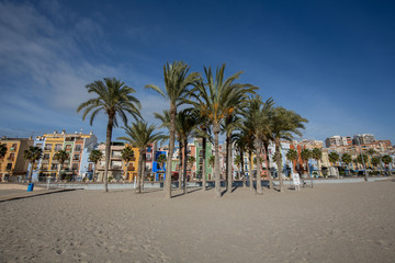Joiosa, Alicante, Spain - 26 december 2017: View on the houses at the beach of the village Joiosa, Alicante, Spain with palms trees in front