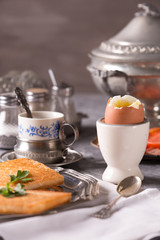 Breakfast with croutons, poached egg and coffee. Vintage dishes.