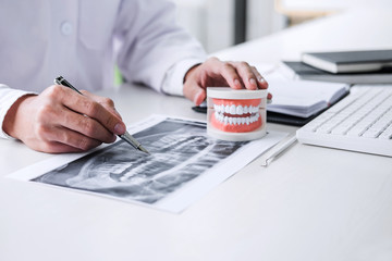 Male doctor or dentist working with patient tooth x-ray film, model and equipment used in the treatment and analysis teeth disease of dental and dentistry at workplace