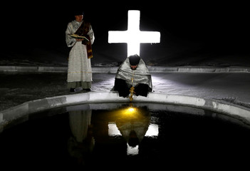 Priest immerses a cross into a lake on the eve of Orthodox Epiphany in Minsk