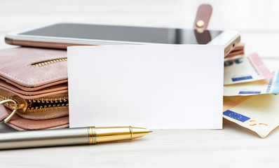 Blank card with woman's purse, smartphone and pen on the table.