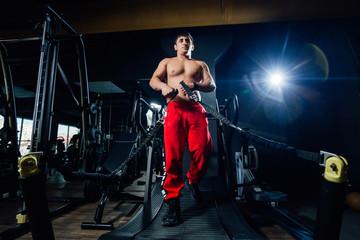 Shirtless man exercising on treadmill