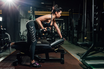 Beautiful young woman in sportswear lifting heavy dumbbell while leaning on bench in dark modern gym