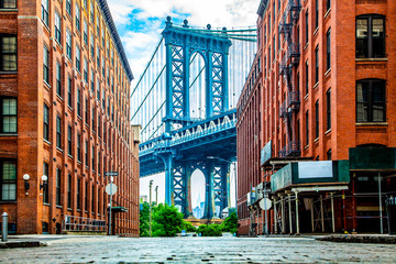 Manhattan Bridge between Manhattan and Brooklyn over East River seen from a narrow alley enclosed by two brick buildings on a sunny day in Washington street in Dumbo, Brooklyn, NYC Wall mural