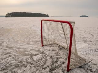 hockey net on the ice of a frozen lake in winter