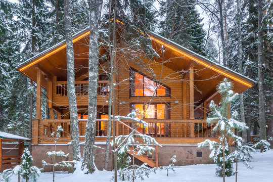 Snow-covered beautiful wooden house in the forest at dusk