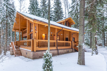 Snow-covered beautiful wooden house in the forest at dusk. Modern log cabin with large decks