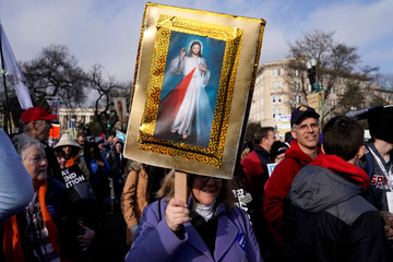 Anti-abortion marcher carries a picture of Jesus Christ during a rally at the Supreme Court during the 46th annual March for Life in Washington
