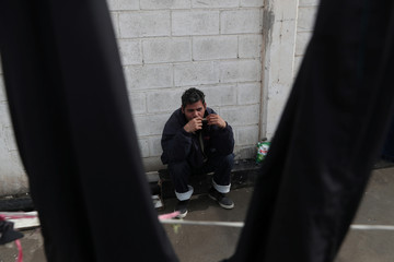 A migrant from El Salvador, part of a caravan of thousands from Central America trying to reach the United States, plays the harmonica at a temporary shelter in Tijuana, Mexico